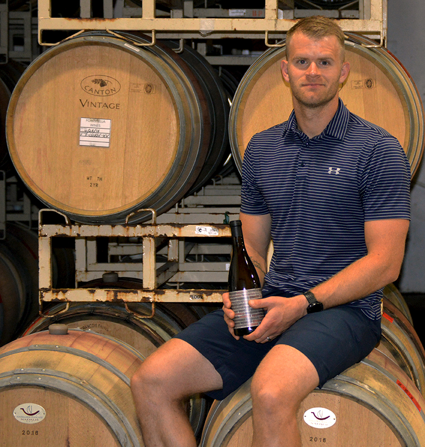 Matt Iaconis posing with a bottle of wine in a barrel room