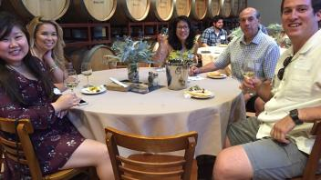 Aggies sitting at a round table near barrels of wine
