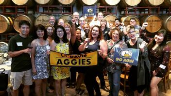 Group of Aggies in front of barrels of wine