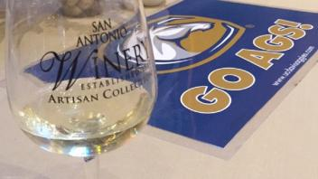Empty wine glass and Go Ags! sign on a table