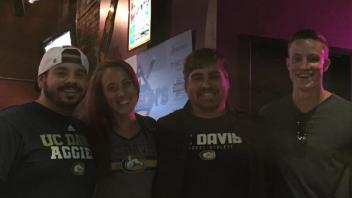 Three men and a women wearing Aggie gear, smiling.