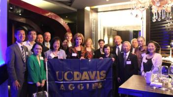 Group of Aggies standing with UC Davis flag