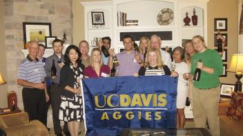 Aggies holding up a UC Davis flag in the living room