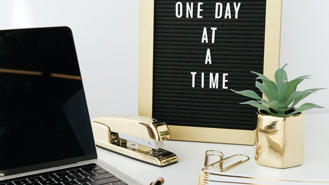 "laptop work station with a sign next to it that says ""one day at a time"""
