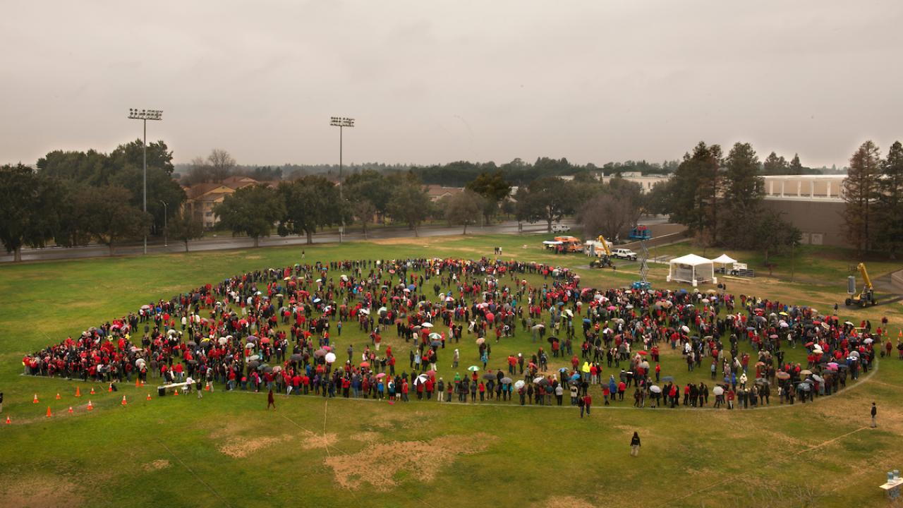 An aerial shot of a group of people forming a heart at Hutchison Field