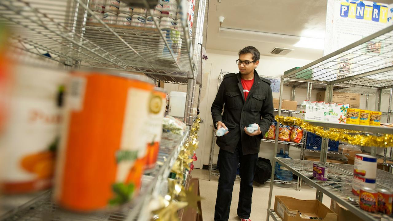 Picture of a student standing between an aisle lined with shelves at The Pantry.