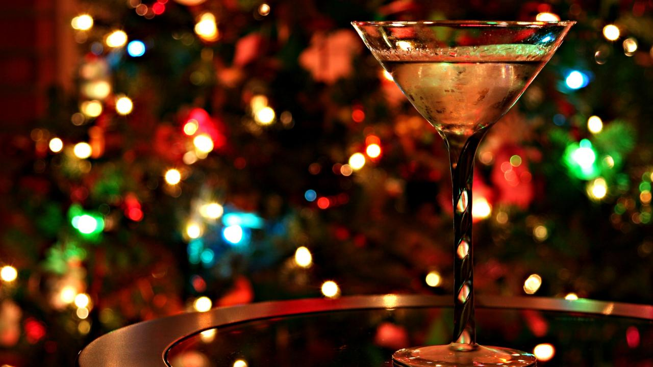 photo of a martini glass in front of a background of twinkle lights