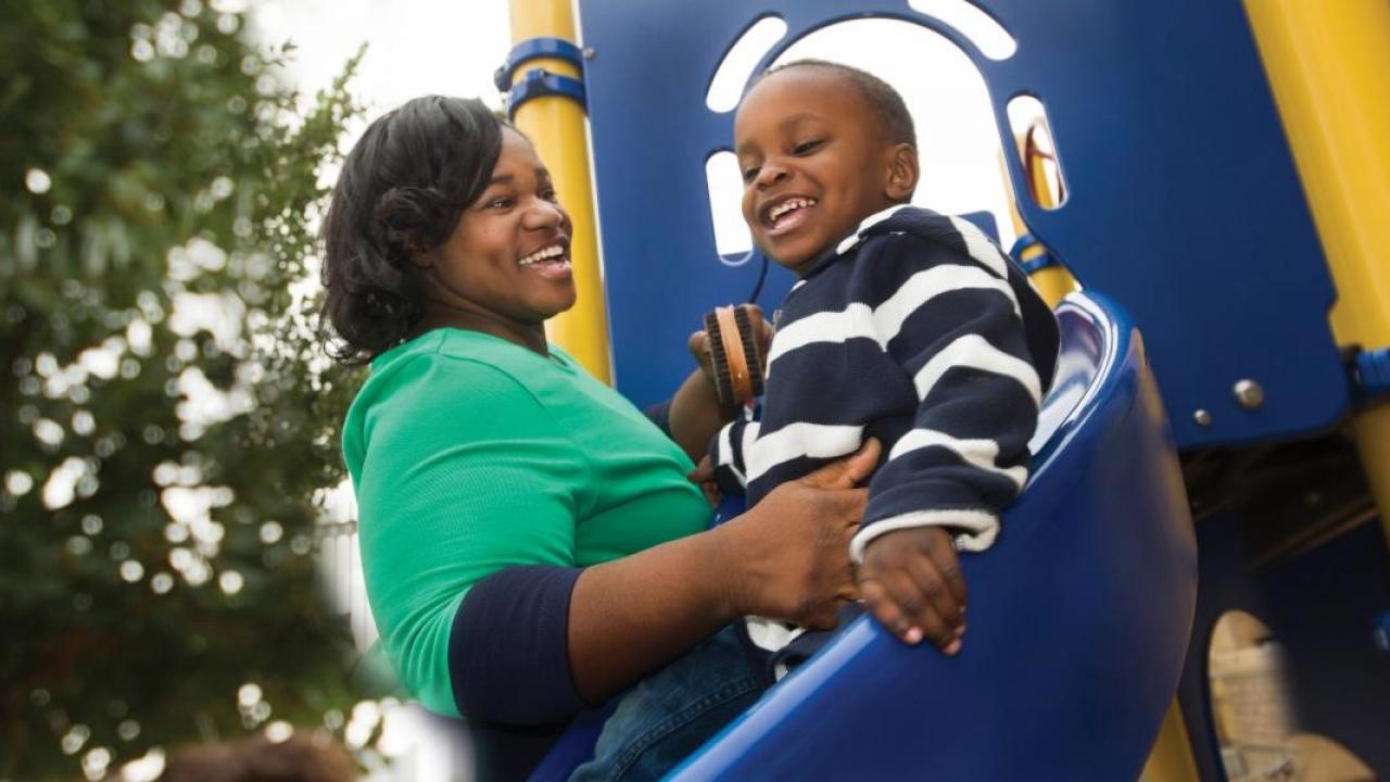 Picture of a women and a boy playing on a slide.