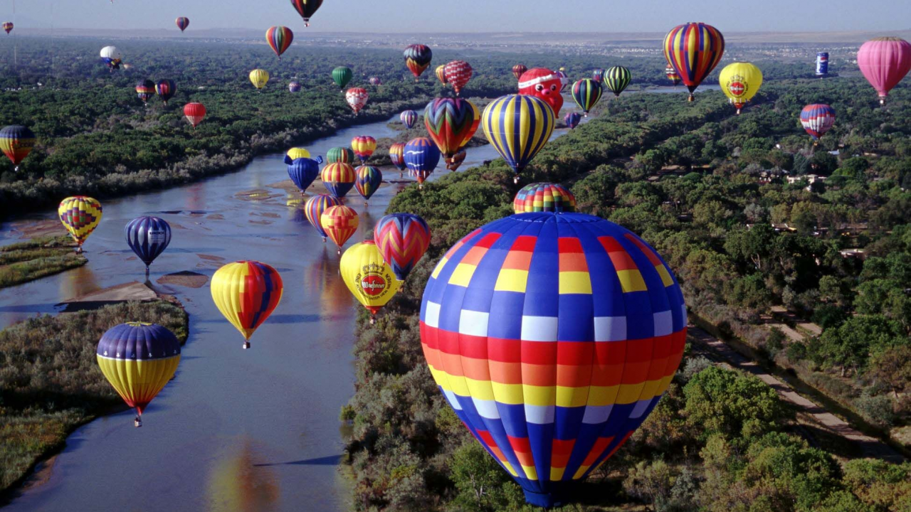 Several hot air balloons flying over water in Albuquerque.