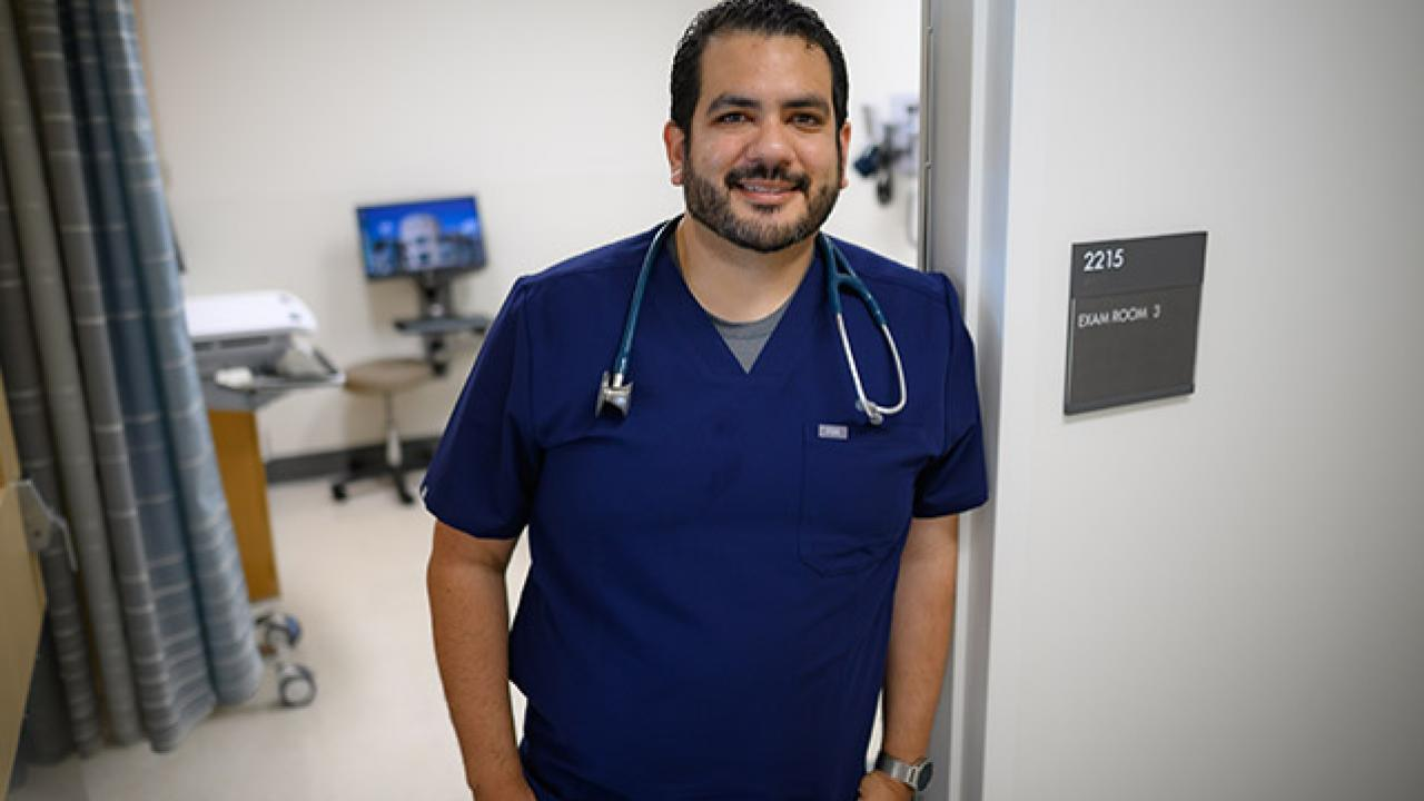 Matthew Vega standing outside a patient room in a medical setting
