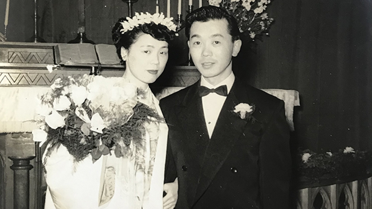 Black and white photo featuring two people in wedding attire with candles and cross behind them.