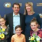 David Nix posing with his family in front of a UC Davis Aggies backdrop