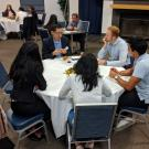 Picture of students and an alumni talking at a table.