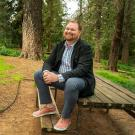 Paul Terry sitting on a bench in the arboretum.