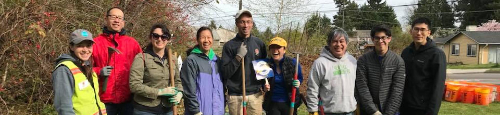 A group of UC Davis alumni in Seattle at a community service day posing with shovels outdoors